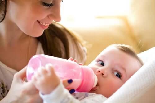 Madre che allatta bambino con biberon.