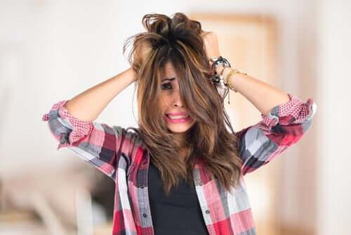Donna nervosa che si tocca i capelli.