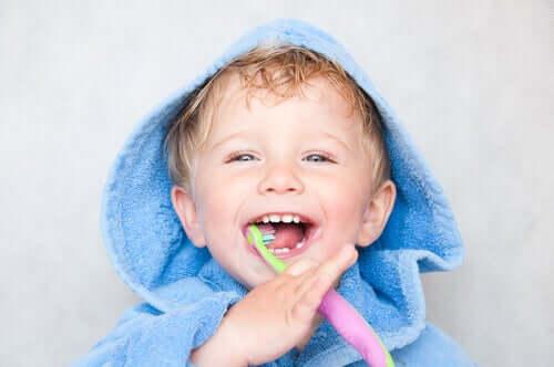 Bambino che si lava i denti con lo spazzolino.