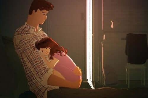 Padre che tiene la figlia in braccio.