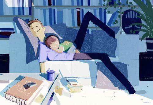 Padre sdraiato con il figlio sul divano.