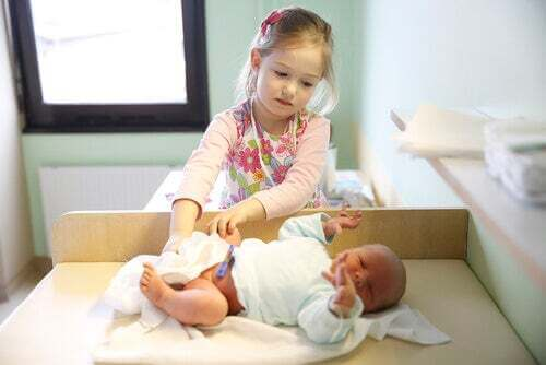 Sorella maggiore che si prende cura del neonato.