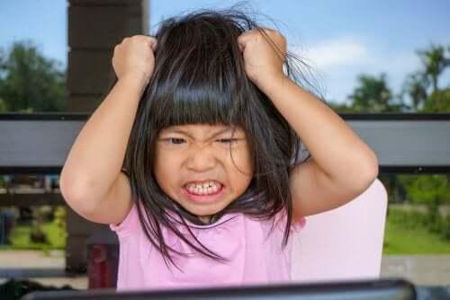 Bambina arrabbiata con le mani in testa che si tira i capelli.