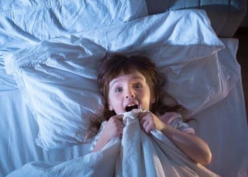 Bambina che si sveglia spaventata a causa di un incubo.