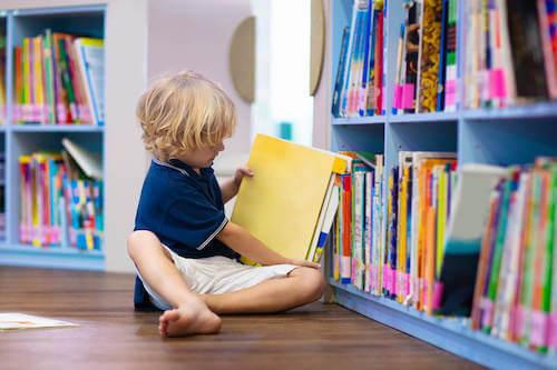 Dall'asilo alla scuola primaria. Bambino che prende un libro dalla libreria della scuola.