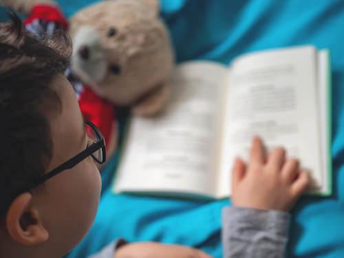 Bambino con gli occhiali che legge un libro.