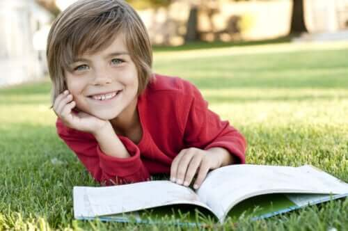 Bambino sorridente che legge un libro in un parco.