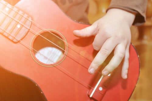 Bambino suona una chitarra. Intelligenze multiple.