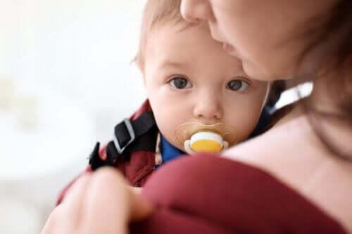 Bambino in braccio alla mamma col ciuccio in bocca.
