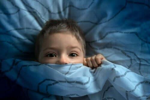 Bambino preoccupato sotto le coperte.
