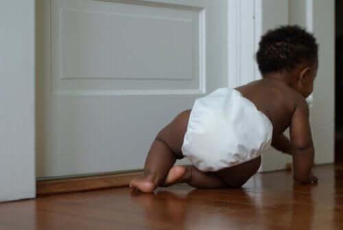 Fasi dello sviluppo del bambino. Bambino col pannolino che gattona.
