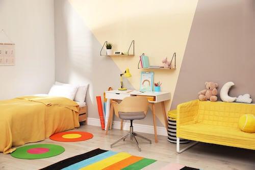 Cameretta del bambino con letto, scrivania e divano giallo.