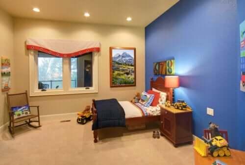 Camera del bambino con parete blu e sedia a dondolo.