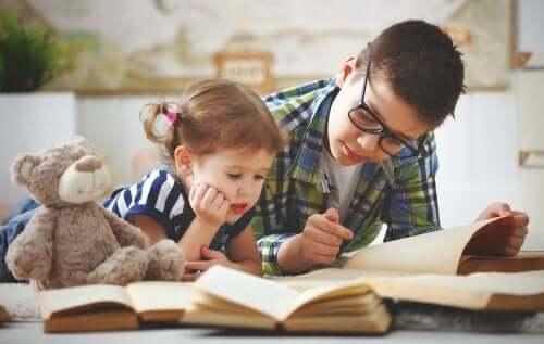 Fratello che legge un libro alla sorella.