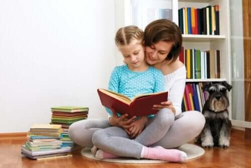 Madre che legge un libro alla figlia. Libreria con libri per bambini.