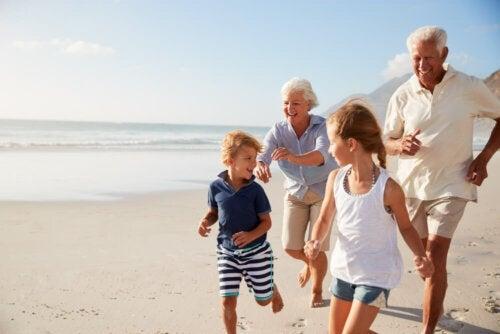 Nonni e nipoti che corrono felici in spiaggia in estate.
