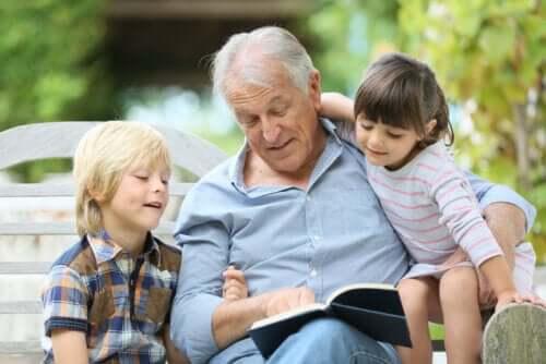 Nonno seduto su una panchina che legge un libro di Gianni Rodari ai nipoti.