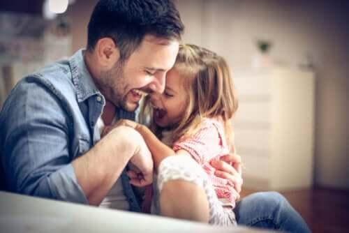 Padre e figlia che giocano e ridono.