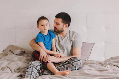 Padre seduto sul letto che tiene in braccio il figlio.