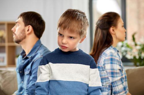 Bambino arrabbiato che volta le spalle ai genitori.