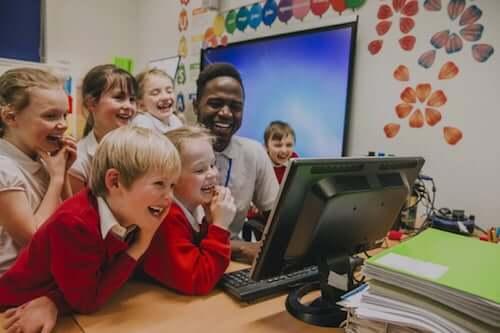Insegnante ed alunni che ridono e fanno lezione davanti ad un computer.