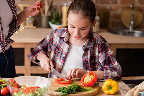 Bambina vegana che taglia le verdure per preparare un'insalata.
