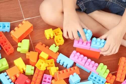 Bambino che gioca con pezzi colorati per costruzioni.