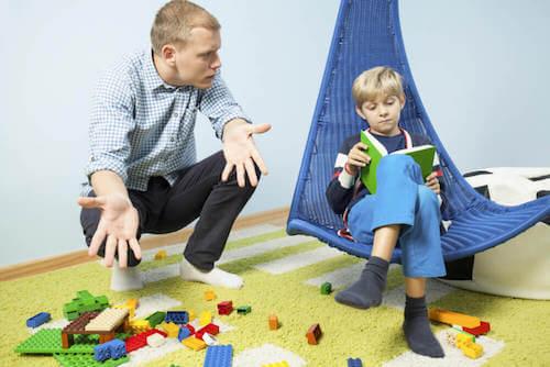 Padre disperato che dice al figlio di mettere a posto i giocattoli.