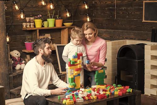 Padre e madre che giocano col figlio facendo le costruzioni.