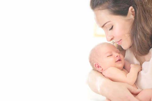 Madre che culla il figlio neonato.