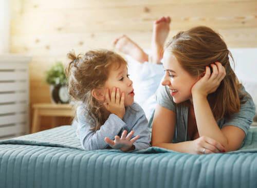Ragazza e bambina parlano sul letto.