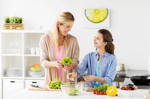 Madre e figlia vegana che preparano un'insalata.