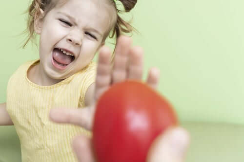 Bambina che si rifiuta di mangiare una mela.