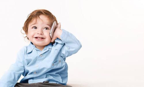 Bambino piccolo che sorride e che parla al telefono.