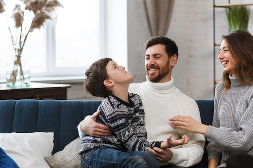 Padre, madre e figlio che giocano e ridono seduti sul divano.