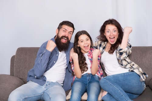 Padre, madre e figlia che si divertono seduti sul divano.
