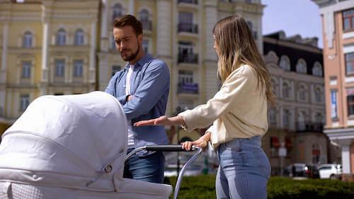 Padre e madre che discutono mentre portano il bambino a fare una passeggiata col passeggino.