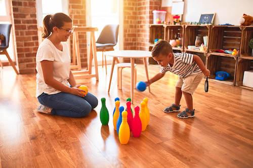 Madre e figlio che giocano con dei birilli colorati.
