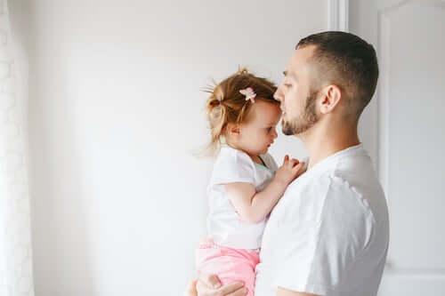 Padre che tiene in braccio la figlia neonata e le dà un bacio.