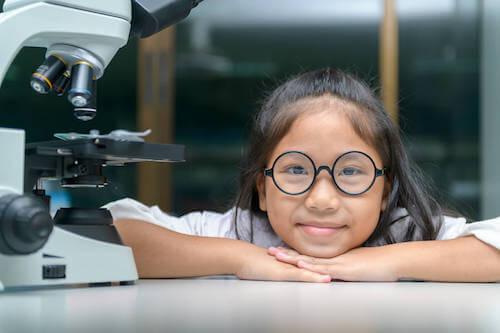 Bambina che ha appena usato un microscopio.