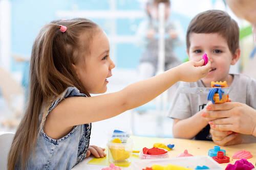 Bambini che giocano modellando e creando degli oggetti con la plastilina.
