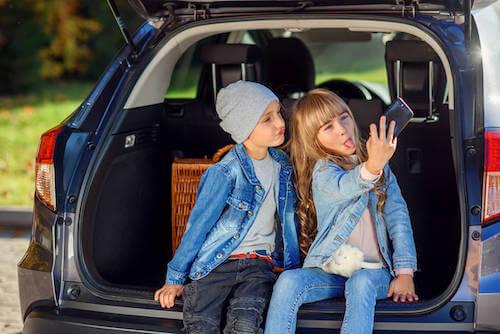 Bambini seduti nel bagagliaio della macchina che si fanno un selfie.