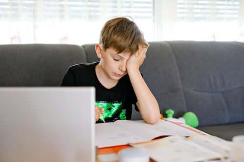 Ragazzo adolescente davanti al computer che ha difficoltà a fare i compiti.