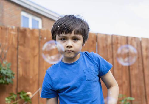Bambino che si diverte giocando con le bolle di sapone.