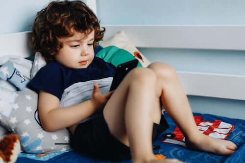 Bambino che usa il telefono sdraiato sul letto.