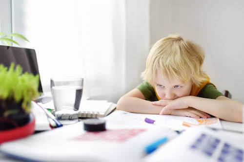 Bambino che non vuole fare i compiti.