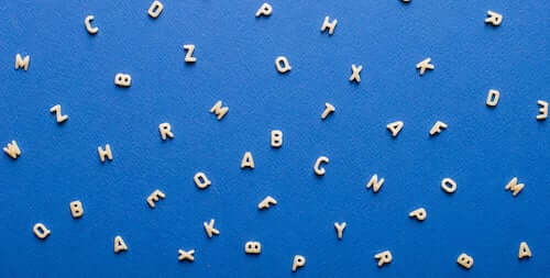 Lettere dell'alfabeto sparse su un foglio blu.