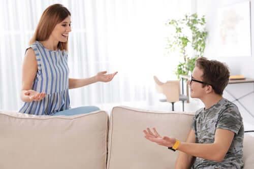 Madre che parla e scherza con il figlio adolescente seduto sul divano.