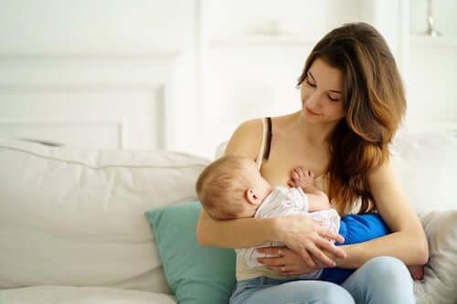 Mamma che allatta al seno il figlio neonato.