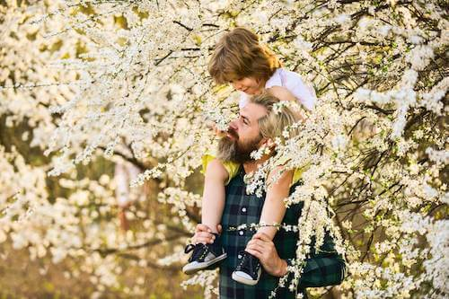 Padre e figlio che passeggiano tra gli alberi fioriti.